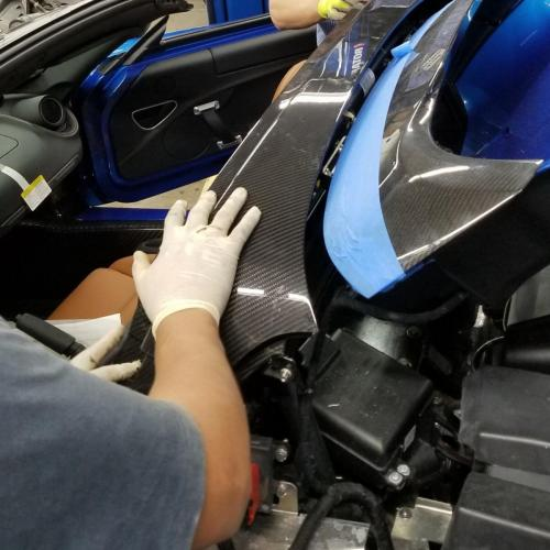 Gus installing a $3,000 carbon fiber trim piece (very carefully) at Alfa-Romeo of Glendale